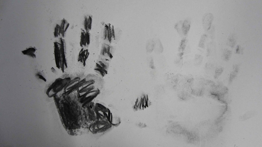 Two hands are beautifully recorded using charcoal dust.