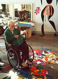 Matisse in his studio making the cut-outs.